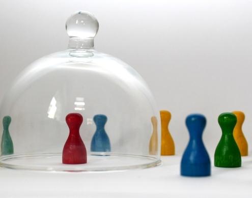 Spielfigur steht unter einer Glasglocke und andere Figuren außerhalb